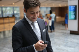 business man uses smart phone to send text on wireless network